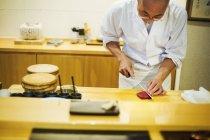 Chef affettare il pesce per fare il sushi — Foto stock