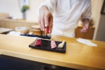 Chef presenting a fresh plate of sushi. — Stock Photo