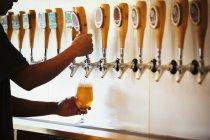 Homem puxando um copo de cerveja — Fotografia de Stock