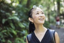 Femme souriante, debout dans une forêt — Photo de stock