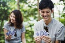 Жінка і чоловік гральних карт у лісі. — стокове фото