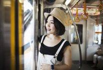 Mulher de chapéu viajando em um trem — Fotografia de Stock