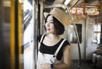 Woman wearing a hat traveling on a train. — Stock Photo