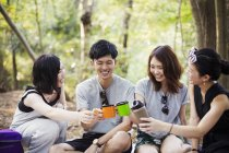 Women and a man sitting in a forest. — Stock Photo
