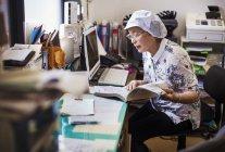Пожилая женщина в офисе фаст-фуд — стоковое фото