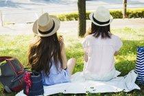 Women sitting on a lawn. — Stock Photo