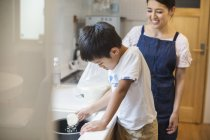 Mother and son standing at a sink. — Stock Photo