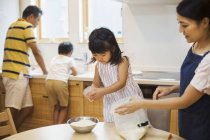 Parents and two children preparing a meal. — Stock Photo