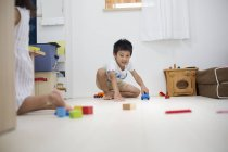 Boy playing with cars on the floor. — Stock Photo