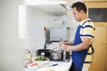 Mann in eine blaue Schürze, eine Mahlzeit zuzubereiten — Stockfoto