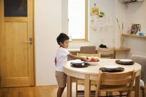 Boy setting the table for a meal. — Stock Photo
