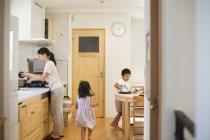 Frau und zwei Kindern in Küche — Stockfoto