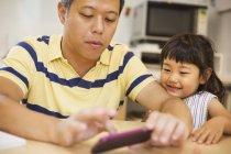 Uomo che per mezzo di un telefono intelligente con la figlia — Foto stock