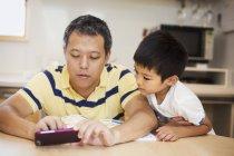 Hombre y su hijo mirando teléfono inteligente - foto de stock