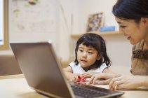 Женщина и ее дочь с ноутбуком — стоковое фото