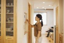 Donna regolare il termostato su una parete — Foto stock
