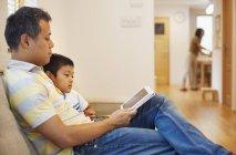 Hombre y su hijo sentado leyendo un libro - foto de stock