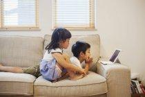 Niño y niña viendo una tableta digital . - foto de stock