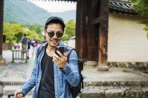 Man in sunglasses with smart phone. — Stock Photo