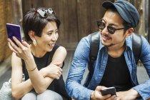 Couple assis côte à côte — Photo de stock