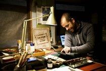Людина в його майстерні, використовуючи цифровий планшетний — стокове фото