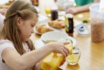Mädchen gießt Orangensaft — Stockfoto