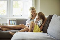 Woman and a child on sofa — Stock Photo