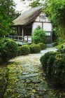 Thatched building in garden — Stock Photo