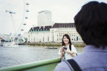 Мужчина и женщина, стоя у реки Темзы — стоковое фото