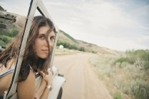 Woman leaning out of moving jeep — Stock Photo