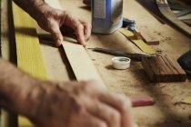 Плотник держит кусок дерева — стоковое фото