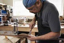 Homme travaillant sur arc en bois — Photo de stock