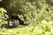 Group of people in shade of trees in garden. — Stock Photo
