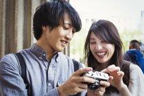 Японский мужчина и женщина держат камеру — стоковое фото
