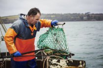 Fisherman opening  fishing creel — Stock Photo