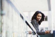 Femme se penchant sur le rail de balcon — Photo de stock