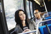Femme et homme assis dans les transports publics — Photo de stock