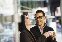 Man and woman holding cellphone and laughing — Stock Photo