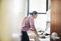 Mann im Büro stehen und stützte sich auf Schreibtisch — Stockfoto