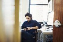 Mann sitzt im Büro und telefoniert, — Stockfoto