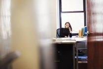 Женщина сидит за столом в офисе — стоковое фото