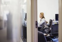 Frau sitzt am Schreibtisch im Büro — Stockfoto