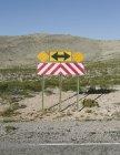 Flèche directionnelle et signe d'avertissement — Photo de stock
