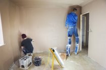 Electrician and plasterer working — Stock Photo