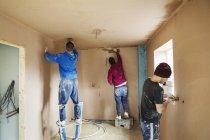 Three men at house under construction — Stock Photo