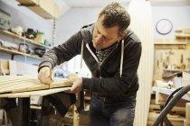 Mann arbeitet in Holzwerkstatt. — Stockfoto