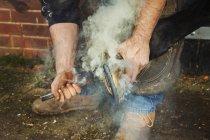 Farrier fitting horseshoe to horse hoof — Stock Photo