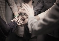 People standing with hands layered in gesture — Stock Photo