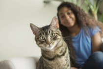 Девушка, сидящая на диване с кошкой — стоковое фото