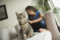 Girl sitting on sofa with cat — Stock Photo